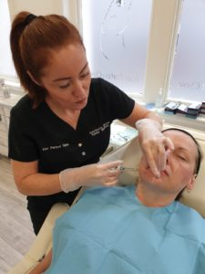 Nurse practitioner injecting dermal fillers treatment